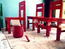 Red wooden chairs and a container of red paint Stock Images