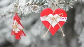 Red wooden christmas toys on snow-covered fir in winter park stock video footage