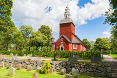 Red wooden church. With a cemetery Royalty Free Stock Image