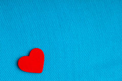 Red wooden decorative heart on blue cloth background. Royalty Free Stock Photos