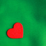 Red wooden decorative heart on green cloth background. Royalty Free Stock Image