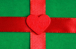 Red wooden decorative heart on green cloth background. Royalty Free Stock Photography