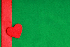 Red wooden decorative heart on green cloth background. Stock Photo