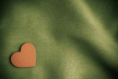 Red wooden decorative heart on green folds background. Royalty Free Stock Image