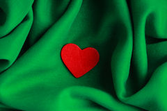 Red wooden decorative heart on green folds background. Stock Photo