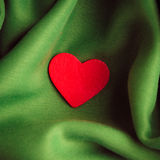 Red wooden decorative heart on green folds background. Stock Photography