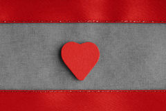Red wooden decorative heart on grey gray cloth background. Stock Photo