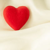 Red wooden decorative heart on white silk background. Royalty Free Stock Photos