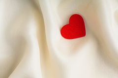Red wooden decorative heart on white silk background. Stock Images