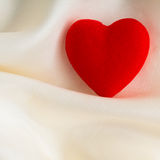 Red wooden decorative heart on white silk background. Royalty Free Stock Photo
