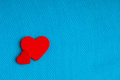 Red wooden decorative hearts on blue cloth background. Royalty Free Stock Image