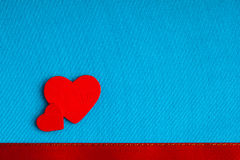 Red wooden decorative hearts on blue cloth background. Stock Images