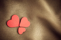 Red wooden decorative hearts on brown folds background. Royalty Free Stock Image