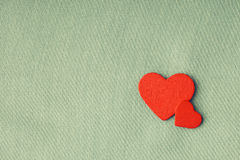 Red wooden decorative hearts on gray cloth background. Stock Photos