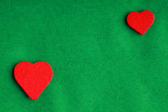Red wooden decorative hearts on green cloth background Stock Image