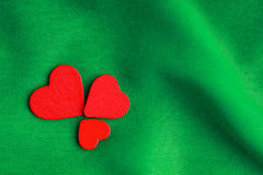 Red wooden decorative hearts on green folds background. Royalty Free Stock Photos