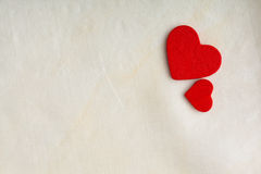 Red wooden decorative hearts on white cloth background. Stock Images