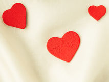 Red wooden decorative hearts on white silk background. Royalty Free Stock Photography
