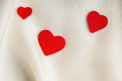 Red wooden decorative hearts on white silk background. Royalty Free Stock Image