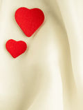 Red wooden decorative hearts on white silk background. Royalty Free Stock Photo