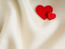 Red wooden decorative hearts on white silk background. Stock Photo