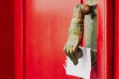 Red door with antique brass knocker in the shape of a hand stock photography