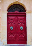 Red wooden door with antique handles, Malta. Old wooden door painted in red, with antique handles, surrounded by yellow stone walls Royalty Free Stock Photography