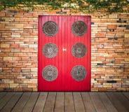 Red wooden door on brick wall Stock Images
