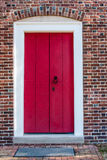 Red, Wooden Door in Brick Wall Royalty Free Stock Photography