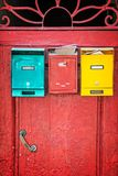 Red wooden door with colorful mailboxes, Florence Italy Stock Photography