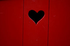 Red wooden door with heart. A closeup view of a wooden door painted rich red with a heart-shaped hole cut or carved in it Stock Photos