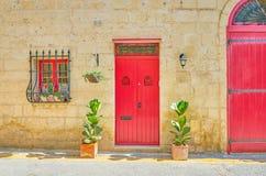 The red door in Naxxar, Malta. The red wooden door of old residential mansion in Naxxar town, Malta stock images