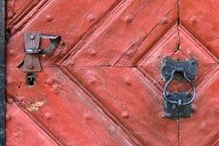 Red wooden door with rustic keyhole, door knocker Royalty Free Stock Images