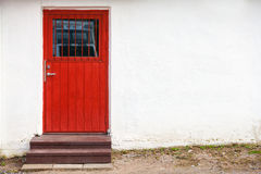 Red wooden door in white rural wall Royalty Free Stock Photography