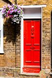 Red wooden doors on the old red bricks house. Flowers on the wall of the house. royalty free stock photography