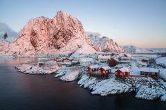 Red wooden fisherman house with snow cover on mountain in Hamnoy village, Norway royalty free stock photography