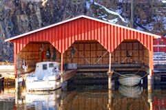 Red wooden garage for three boats Stock Photo