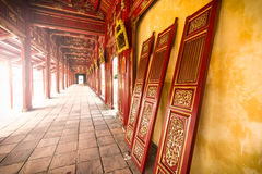 Red wooden hall of Hue citadel in Vietnam, Asia. Beautiful red wooden hall with golden ornate details in Hue citadel, Vietnam, Asia. Vanishing roof and tiled royalty free stock images