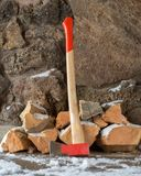 Axe in front of firewood pile stock photos