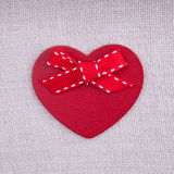 A red wooden heart with a bow on fabric surface Royalty Free Stock Photos