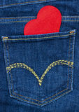 Red wooden heart coming out of denim jeans pocket Royalty Free Stock Images