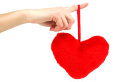 Red wooden heart hanging down from female hand. Close-up of red wooden heart hanging down from female hand (isolated Royalty Free Stock Images