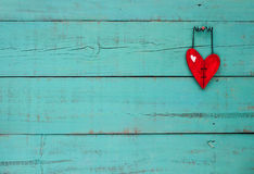 Red wooden heart hanging on turquoise background Stock Images