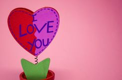 St. Valentine`s Day. Red wooden heart with the inscription `love`. On a pink background. Red wooden heart with the inscription `love`. On a spring with a stock photography