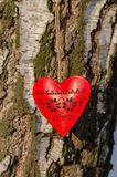 Red wooden heart with ornament on birch bark background stock photography
