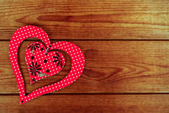 Red wooden heart placed on a brown wood board stock photo