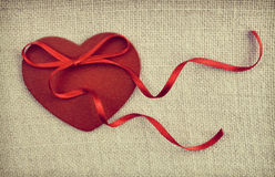 A red wooden heart with a ribon bow on vintage fabric  backgroun Stock Photography