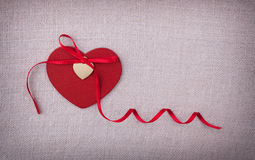A red wooden heart with a silk ribon bow on it Royalty Free Stock Images