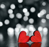 Red wooden hearts against defocused lights. Royalty Free Stock Photo