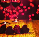 Red wooden hearts with glass and lights in the background. Red wooden hearts on wooden table with red lights and glass of wine in the background Royalty Free Stock Photo